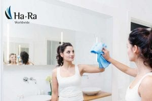 Housekeeper cleaning mirror with a Ha-Ra microfibre cloth